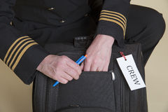 Pilot's hands checking carry on bag Stock Photography