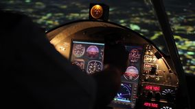 Pilot's hands on steering wheel, night flight, airplane hovering above city stock video