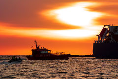 Pilot ship catches big container ship. During hot sunset, Latvia stock photography
