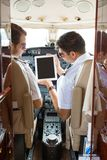 Pilot Showing Digital Tablet To Copilot In Cockpit stock photography