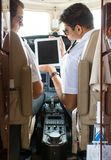 Pilot Showing Digital Tablet To Copilot In Cockpit Royalty Free Stock Image