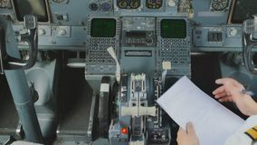 Pilot sits in cockpit and checks documents before flight. Captain of airplane prepares to flight and checks some documents. The man is sitting in cockpit and stock video footage