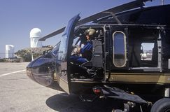 A pilot sitting in the cockpit of the Night Hawk helicopter used by the U.S. Customs Department at a Kitt Peak, Arizona, heliport Stock Image