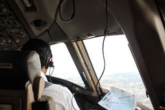 Pilot sitting on a jumpseat in flight deck with headphones, comm. Unicating with tower, looking through a aircraft window, just before landing Royalty Free Stock Images