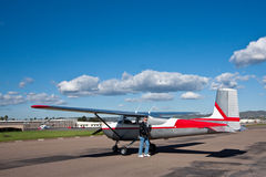Pilot and small airplane. A pilot stands by a Cessna 172 preparing for takeoff at the airport.  Beautiful blue sky with white clouds make a perfect day to be Royalty Free Stock Photos