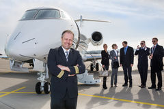 Pilot standing in front of corporate private jet. And smiling to camera Stock Images