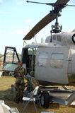 Pilot standing next to ground attack helicopter. US Army military base in Middle East with helicopters stock photography