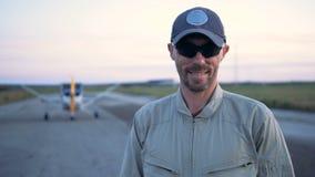 Pilot steht auf einem Flugzeughintergrund und lächelt an der Kamera Porträt eines weiblichen Piloten stock video footage