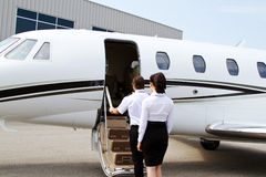Pilot and stewardess entering private jet Stock Image
