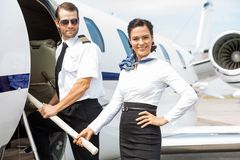 Pilot and Stewardess on Private Jet. Portrait of beautiful airhostess with pilot boarding private jet Stock Images