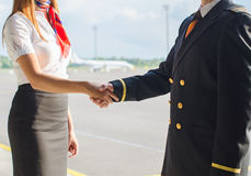 Pilot and stewardess shaking hands. Stock Photos