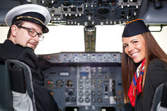 Pilot and stewardess sitting in an airplane cabin. Smiling pilot and stewardess sitting in an airplane cabin Royalty Free Stock Photography