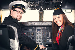 Pilot and stewardess sitting in an airplane cabin. Smiling pilot and stewardess sitting in an airplane cabin toned Stock Photo