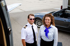 Pilot and stewardess standing outside airplane Royalty Free Stock Photo