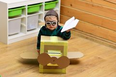 Pilot travel, airdrome, imagination. Little boy child play in cardboard plane, childhood. Air mail delivery, aircraft construction. Kid, pilot school royalty free stock image