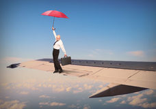 Pilot with umbrella balancing on airliner wing. Hilarious view from aircraft window. Passenger or pilot with umbrella balancing on airliner wing. Travel Stock Image