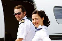 Pilot- und des Stewardesseshereinkommendes Flugzeug Lizenzfreie Stockfotografie