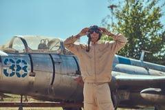 Pilot in uniform and flying helmet standing near an old war fighter-interceptor in an open-air museum. Stock Photography