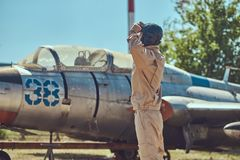 Pilot in uniform and flying helmet standing near an old war fighter-interceptor in an open-air museum. Royalty Free Stock Images