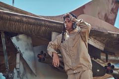 Pilot in uniform and flying helmet standing near an old war fighter-interceptor in an open-air museum. Royalty Free Stock Image