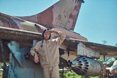 Pilot in uniform and flying helmet standing near an old war fighter-interceptor in an open-air museum. Stock Photo