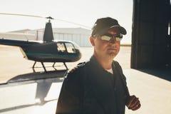 Pilot in uniform standing in airplane hangar Royalty Free Stock Photos