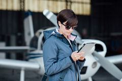 Pilot using aviation apps. Confident female pilot in the hangar doing a pre-flight preparation, she is connecting and using aviation apps on her digital tablet Royalty Free Stock Photography