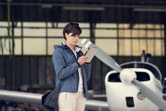 Pilot using aviation apps. Confident female pilot in the hangar doing a pre-flight preparation, she is connecting and using aviation apps on her digital tablet Stock Photo