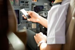 Pilot Using Cell Phone i cockpit royaltyfri fotografi