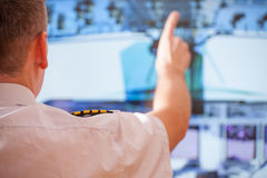 Airline pilot. Pilot wearing uniform with epauletes, sitting inside airline during flight royalty free stock photos