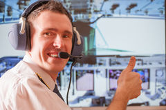 Airline pilot. Pilot wearing uniform with epauletes, sitting inside airliner, thumb up, with visible cockpit during flight Stock Photos