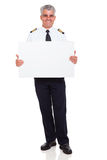 Pilot white board. Smiling senior airline pilot captain holding white board on white background Royalty Free Stock Images