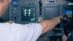 A pilot works in a cockpit, close up. One man sits in a cockpit of a plane simulator stock footage