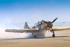 Pilot of Yak 52 airplane from the team Iacarii Acrobati salutes the crowd. With smoke after performing a demonstration flight at Timisoara Airshow, Romania Royalty Free Stock Photo