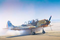Pilot of Yak 52 airplane from the team Iacarii Acrobati salutes the crowd. With smoke after performing a demonstration flight at Timisoara Airshow, Romania Royalty Free Stock Images