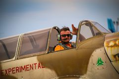 Pilot of Yak 52 airplane from the team Iacarii Acrobati salutes the crowd. With smoke after performing a demonstration flight at Timisoara Airshow, Romania Royalty Free Stock Photography
