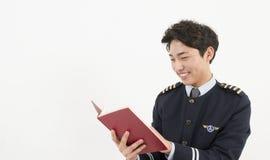 Pilota asiatico di linea aerea che legge un libro Immagine Stock Libera da Diritti