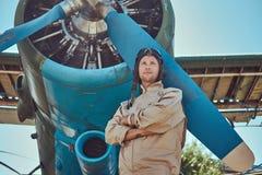 Pilota bello coraggioso in un ingranaggio pieno di volo che sta con le armi attraversate vicino all'aeroplano militare immagine stock libera da diritti
