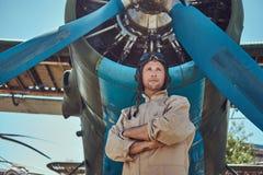 Pilota bello coraggioso in un ingranaggio pieno di volo che sta con le armi attraversate vicino all'aeroplano militare immagini stock libere da diritti