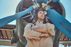 Pilota bello coraggioso in un ingranaggio pieno di volo che sta con le armi attraversate vicino all'aeroplano militare fotografie stock libere da diritti