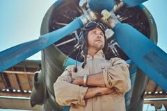 Pilota bello coraggioso in un ingranaggio pieno di volo che sta con le armi attraversate vicino all'aeroplano militare fotografia stock libera da diritti