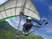 Pilota di deltaplano che sale i updrafts termici sopra il supporto verde immagine stock libera da diritti