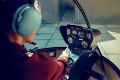 Pilota femminile con esperienza risoluto osservando informazioni sul cruscotto fotografia stock