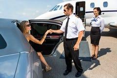 Pilota Helping Elegant Woman che fa un passo dall'automobile Fotografia Stock Libera da Diritti