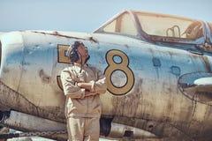Pilota nel casco di volo e dell'uniforme che sta vicino ad un vecchio combattente-intercettore di guerra in un museo all'aperto fotografia stock libera da diritti