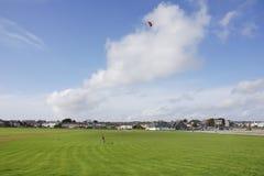 Pilotando un aquilone rosso su nel cielo immagini stock