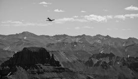 Pilotare un piano vicino a Rocky Mountain Peaks Immagine Stock