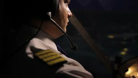 Pilote attentif de capitaine dans le casque dirigeant l'avion de ligne énorme la nuit, fonctions du travail clips vidéos