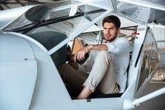 Pilote attirant de jeune homme dans de petits avions Image stock