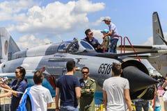 Pilote d'avion de chasse décrivant ses avions aux enfants Image stock